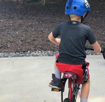 A little boy wearing a helmet while riding a bike.
