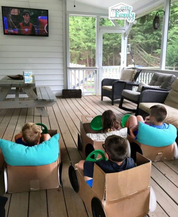 A group of kids sitting in homemade cardboard cars watching television on a porch.