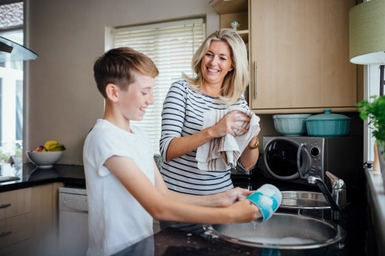 A woman and a boy doing dishes.