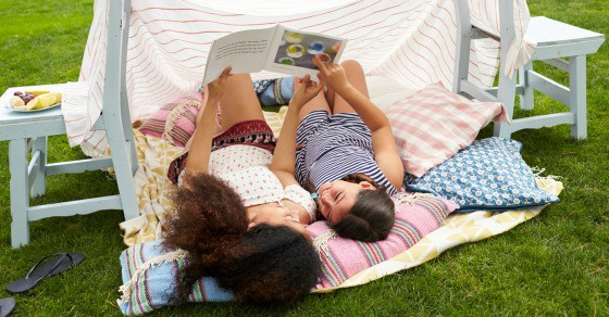 Two girls lying on a blanket outside while reading a book.