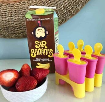 A bowl of strawberries and a container of chocolate milk beside freezer pop molds.