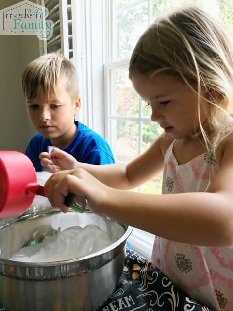 Child adding ingredients into a metal bowl.