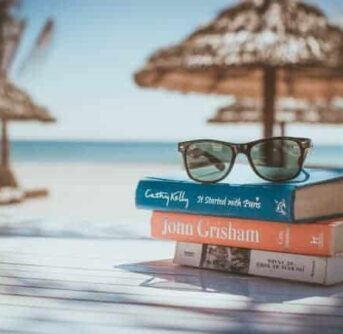 A stack of books with sunglasses resting on them with beach umbrellas and ocean behind them.
