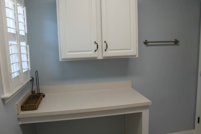 A white counter with a cabinet above it.