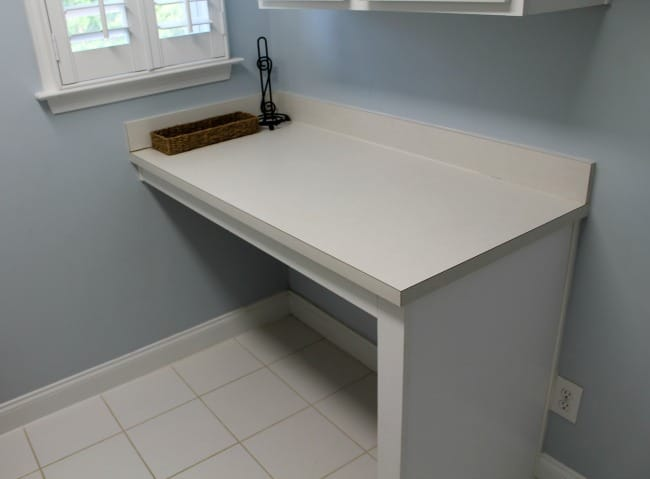 A white counter with a wicker tray on it.