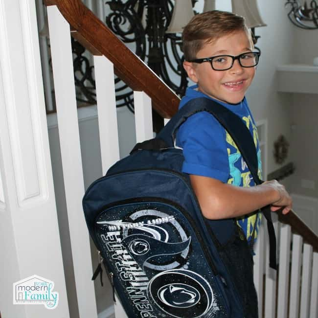 A young boy standing on the stairs with a new backpack.