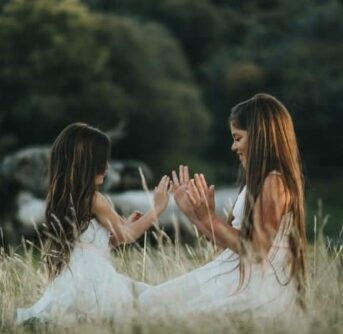 Two girls in white dresses kneeling in a field touching hands.