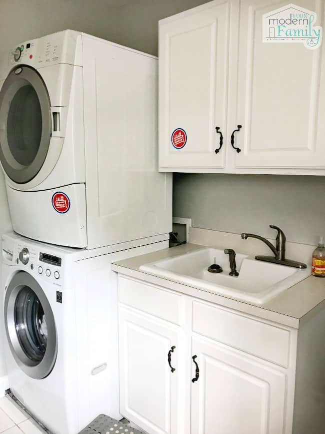 A view of a laundry room with a stacked washer and dryer with a sink and cabinet beside them.