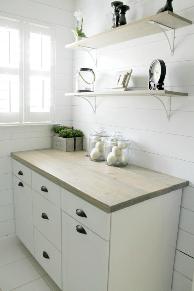 A laundry room counter and shelving above it.