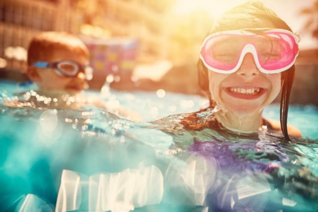 Family activities - kids in goggles playing in the pool in the summertime