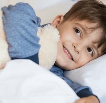 A boy holding a teddy bear lying on a bed.