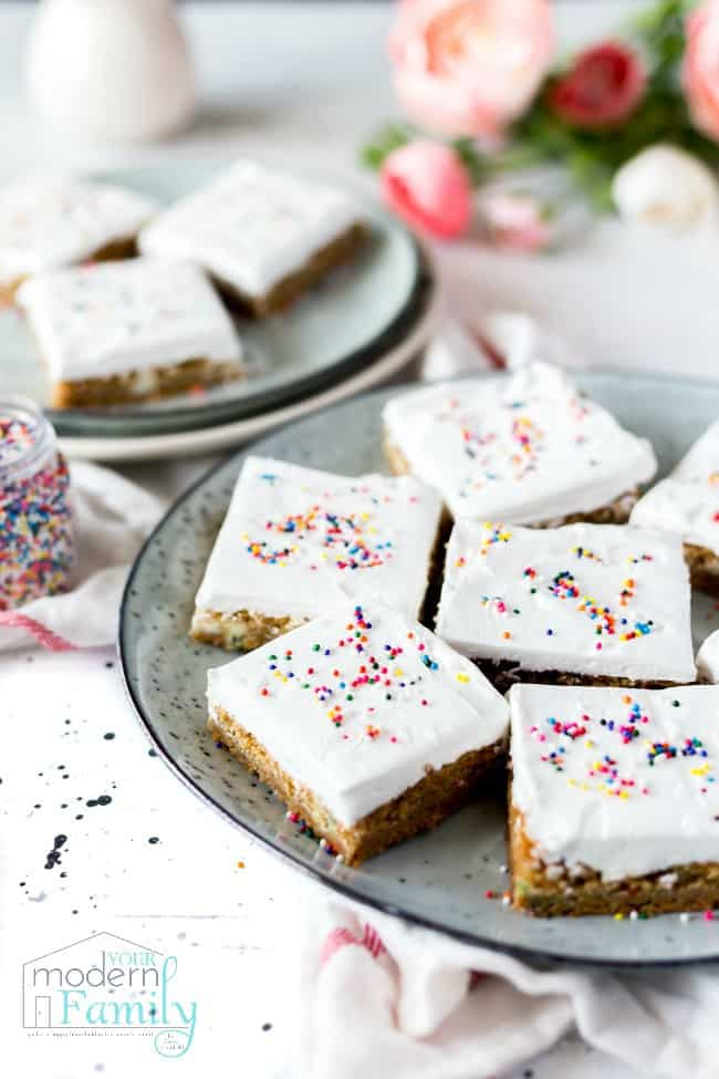 Plates filled with square pieces of iced cake.