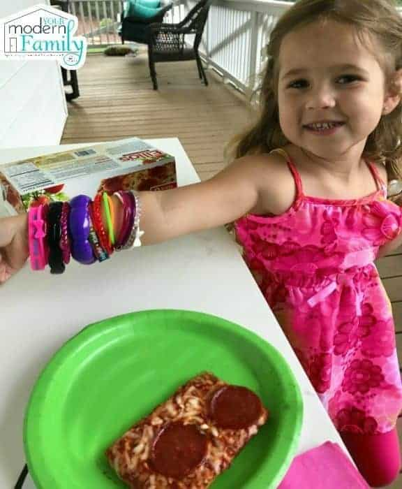 A little girl standing at a table with pizza in front of her.