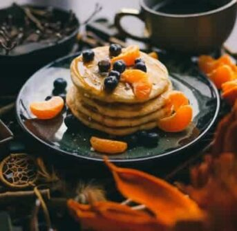 A large stack of pancakes with oranges and blueberries on them.