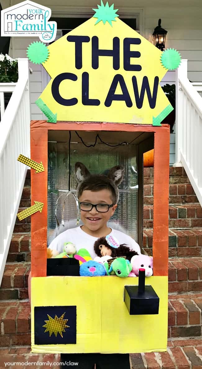 A young boy dressed as a Claw Machine for Halloween.
