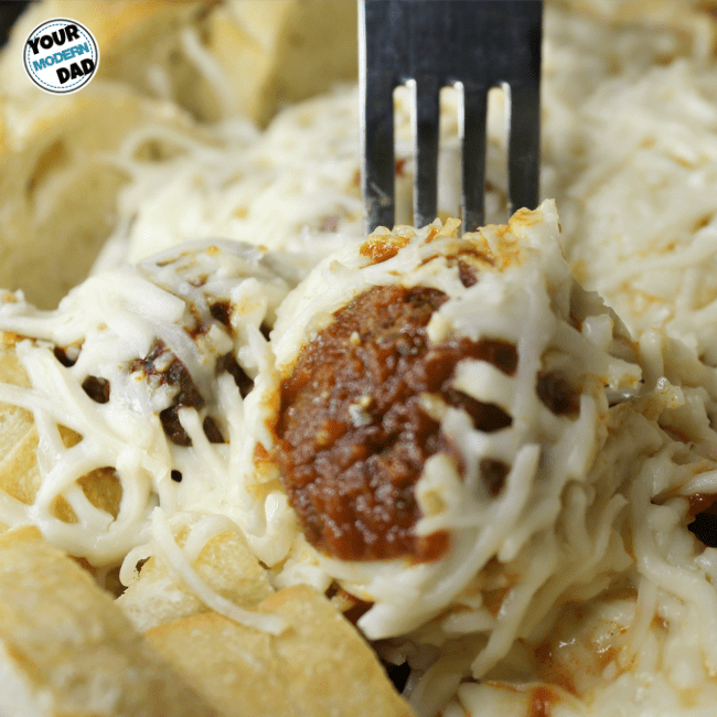 A close up of a plate with a meatball with melted cheese and noodles.
