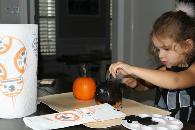 A young girl painting a pumpkin.