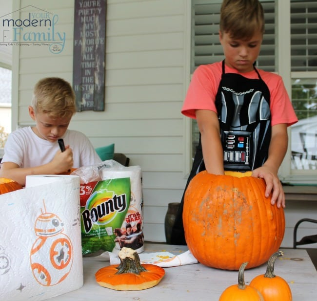 A young boy standing at a table cleaning out a pumpkin.
