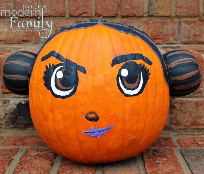 A decorated pumpkin  sitting on top of  brick steps.
