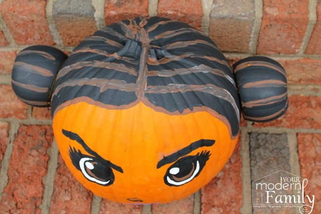 A close up of a completed Princess Leia pumpkin sitting on brick steps.