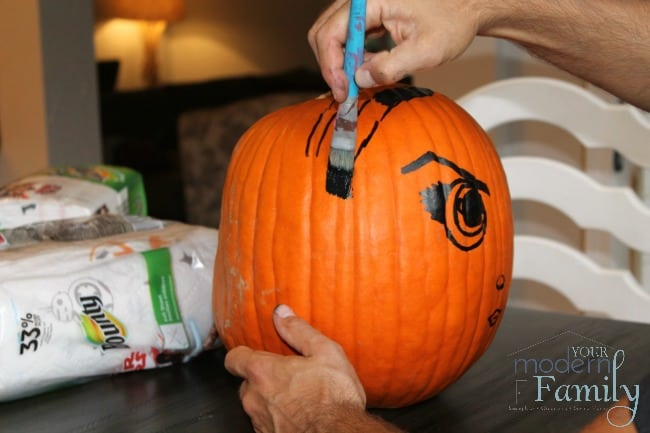 Person decorating a Pumpkin of Princess Leia with black paint.