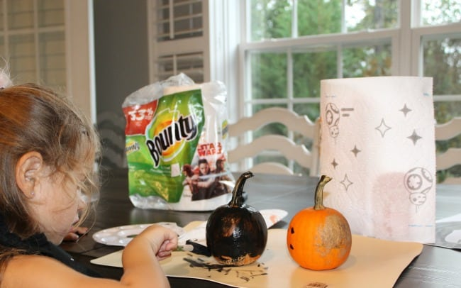 Decorated pumpkins with paper towel roll sitting on a table.