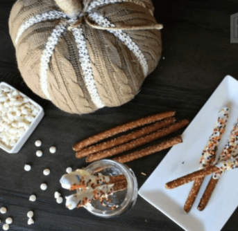 Cinnamon sticks on a white plate with a pumpkin decoration beside them on a wooden table.