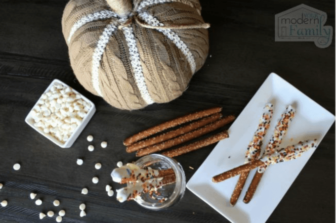 Cinnamon sticks on a white plate with a pumpkin decoration sitting beside them.