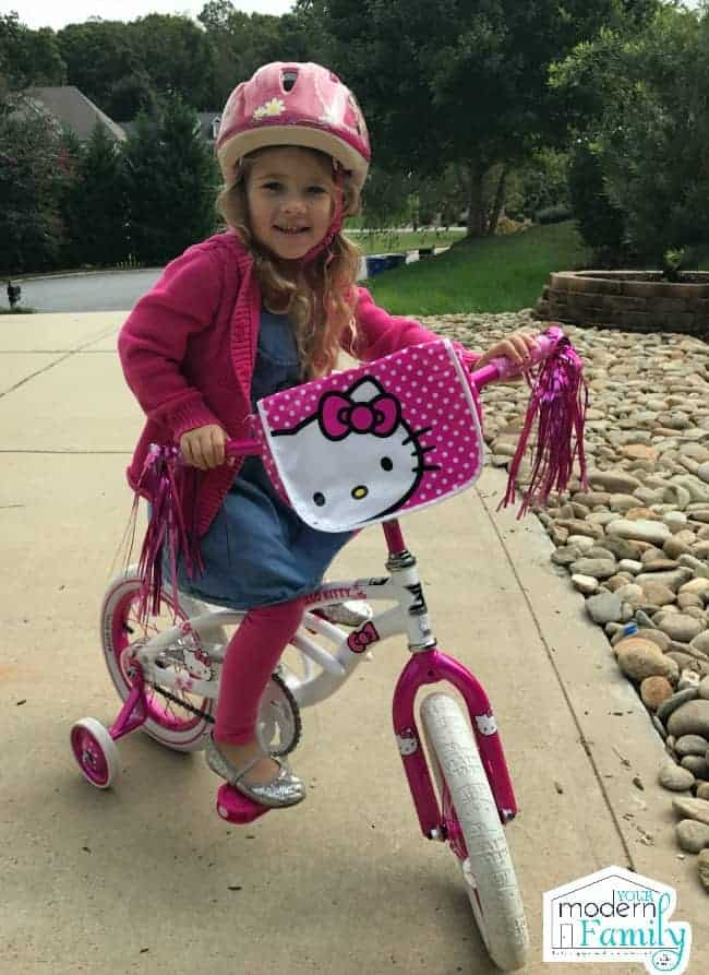 A little girl riding a bike in the driveway.