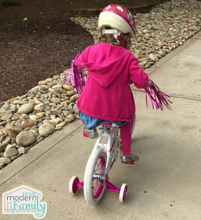 A little girl riding a bicycle with training wheels.
