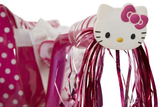 A close up of Hello Kitty bicycle handle bar decorations.