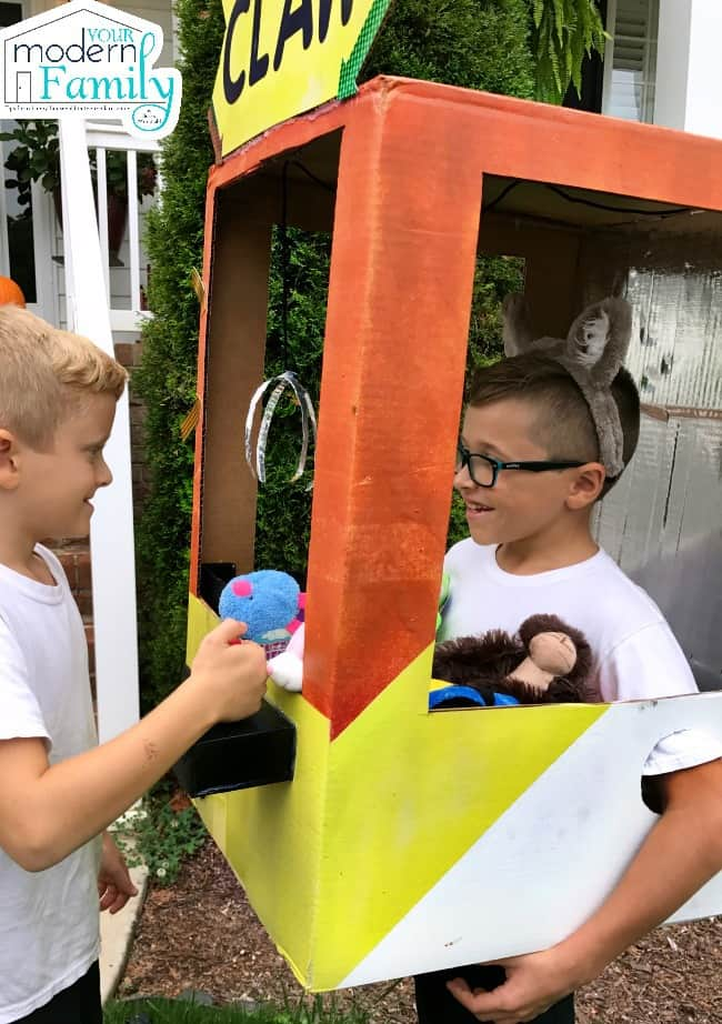 A young boy dressed as a Claw Machine for Halloween as another boy pretends to play the game.