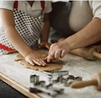 Close up of a woman and a child making Christmas cookies.