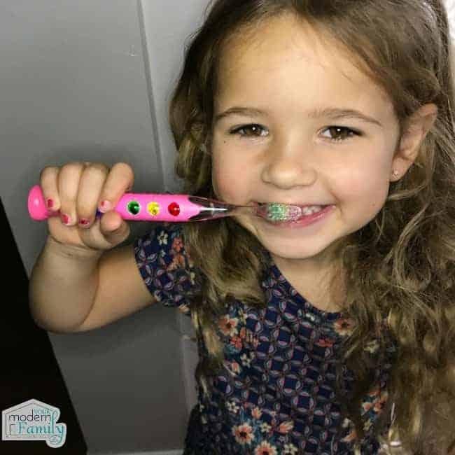 A little girl brushing her teeth.