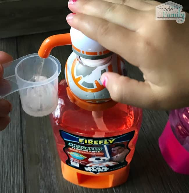 A hand pumping Anti cavity rinse into a small cup.