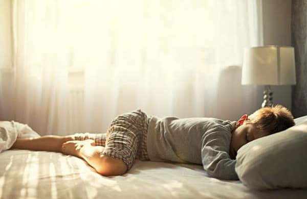 A little boy lying on a bed sleeping.