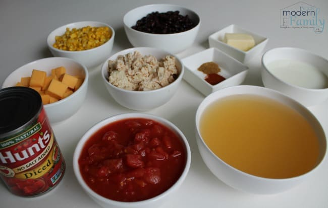 A variety of ingredients in white bowls sitting on a table.