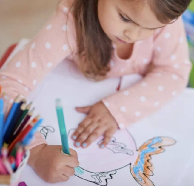 a little girl coloring a picture of a fish
