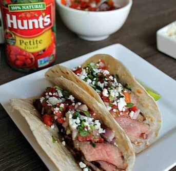 A plate of Tacos with a can of diced tomatoes beside it.
