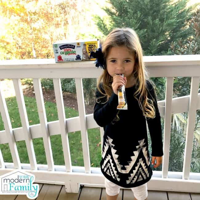 A little girl standing on the porch eating a tube of yogurt.