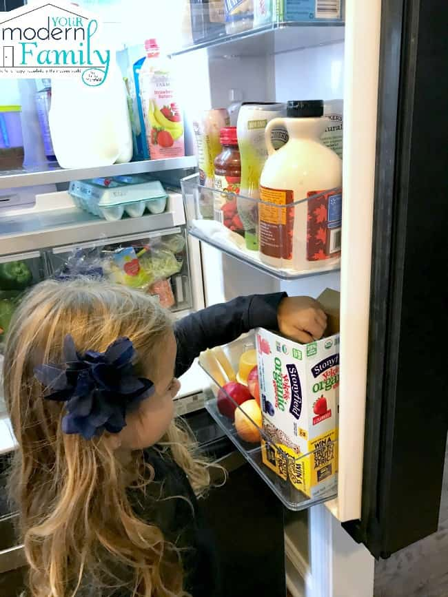 A little girl reaching for a yogurt from the refrigerator.