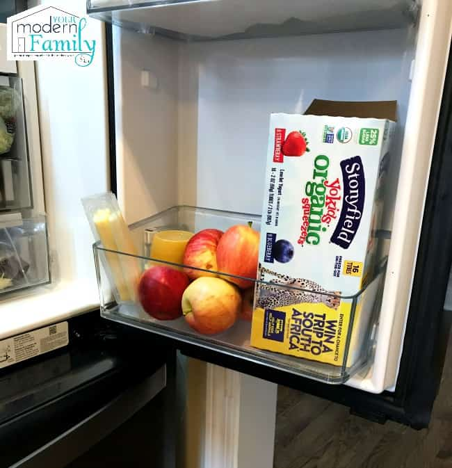 An open refrigerator filled with fruit and yogurt.