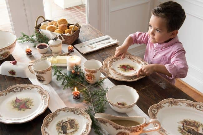 A child sitting at a table with a plate of food, with Dining room and Farmhouse