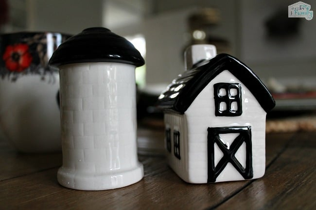 A white ceramic barn and silo decoration on a table.