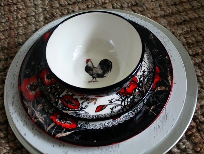 A bowl and plates decorated with roosters and flowers.