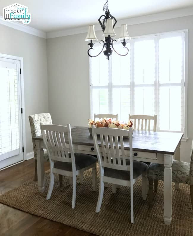 A dining room table in front of a window.
