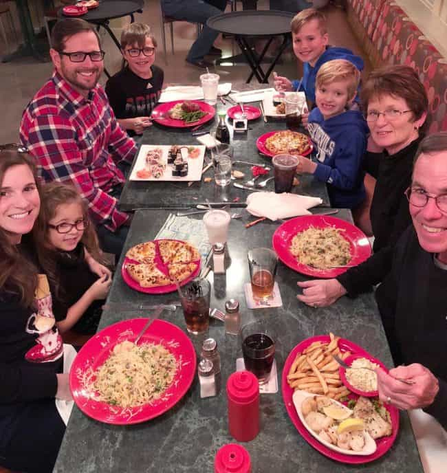 A group of people sitting at a table eating dinner.