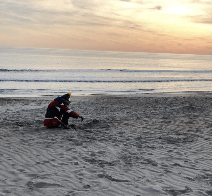 A little boy digging in the sand at sunset.