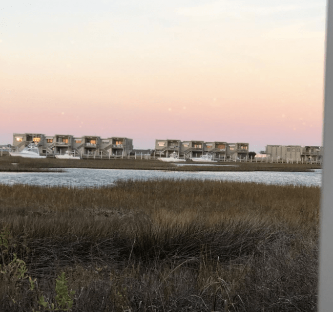 A view of vacation homes from across the marsh .
