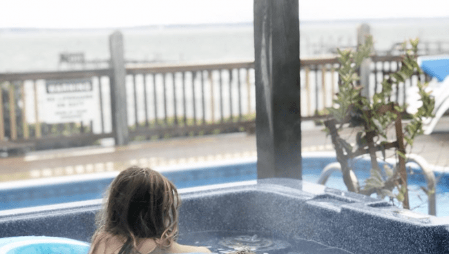 A  little girl sitting in a hot tub with the ocean in the background.